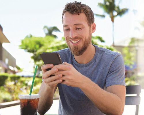Man smiling while he completes a transaction on his phone