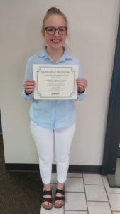 Scholarship winner Macy Landt holding certificate and scholarship check