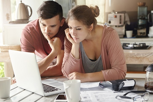 Serious Man And Woman Sitting At Kitchen Table In Front Of Open