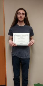 Scholarship winner Sean Tanke holding certificate and scholarship check
