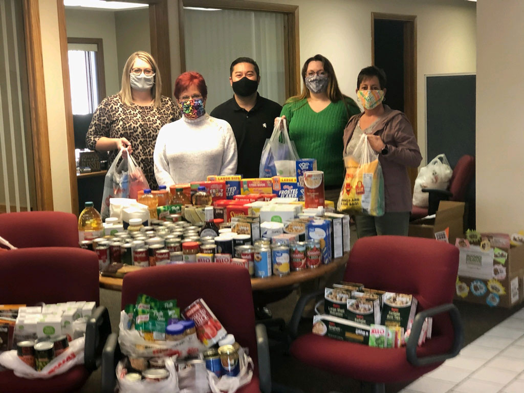 employees standing by a table full of non-perishable foods